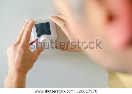 Electrician fitting a thermostat