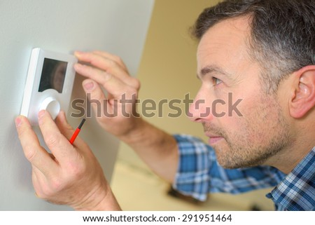 Electrician fitting a thermostat system - stock photo
