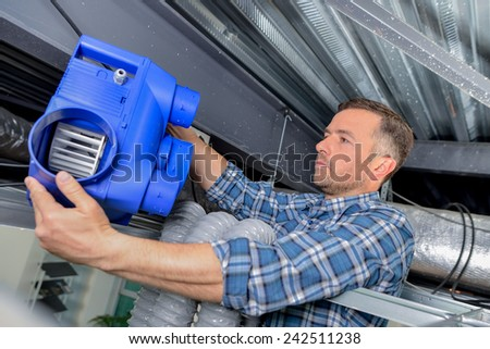 Electrician fitting a ventilation system - stock photo