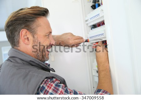 Electrician fixing electric panel in private home