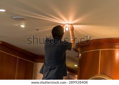 Electrician fixing lights in ceiling - stock photo