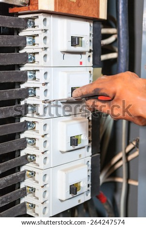 Electrician hand in rubber glove screwing with screwdriver in high voltage box - stock photo