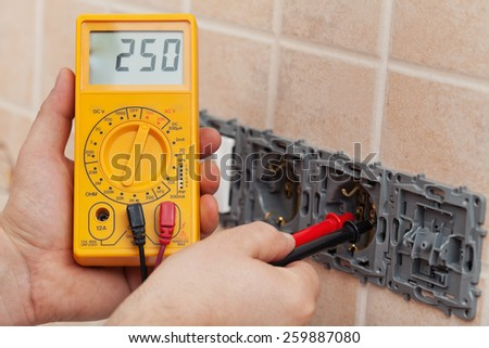 Electrician hands with multimeter measuring the voltage in a partially installed wall fixture - closeup - stock photo