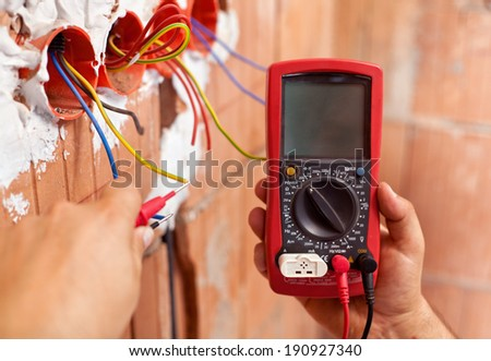 Electrician hands with multimeter measuring the wires in a new building - closeup - stock photo