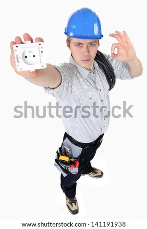 Electrician holding an electrical socket - stock photo