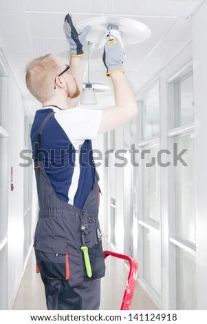 Electrician in Coverall Repairing Broken Light - stock photo
