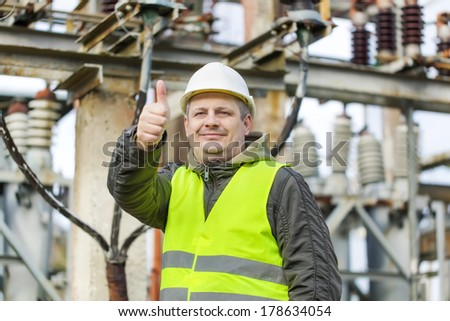 Electrician in electrical substation near to high-voltage cable - stock photo