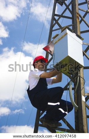 Electrician in red helmet working on electric power pole  - stock photo