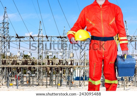 Electrician in uniform holding toolbox at power plant - stock photo