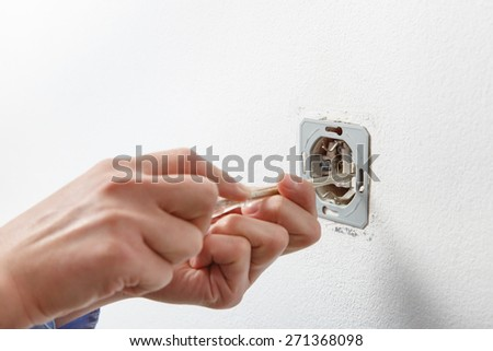 Electrician installing a wall-mounted AC power socket with a screwdriver on a white wall, renovating home.