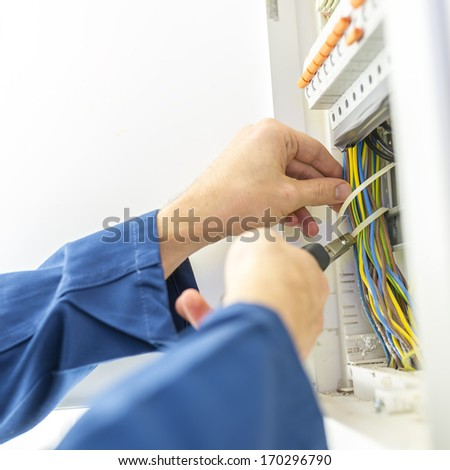 Electrician installing an electrical fuse box in a house working with pliers on the wiring circuits - stock photo