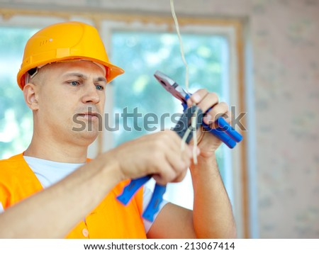 electrician installing electricity in a new house - stock photo