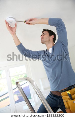 Electrician installing fire alarm inside house - stock photo