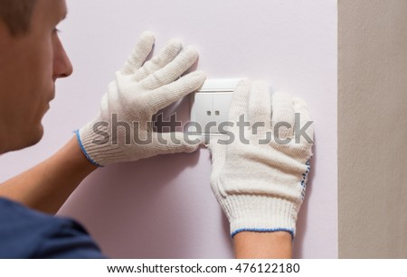 Electrician installing light switch, close up photo