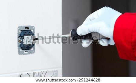 Electrician installing new current socket with screwdriver. - stock photo