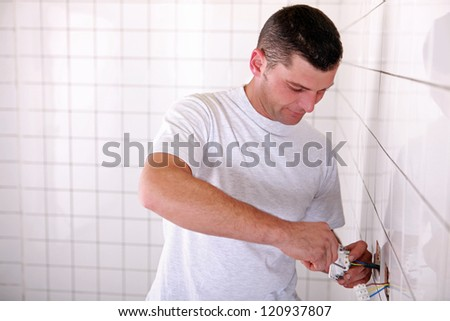 electrician installing outlet in tiled space