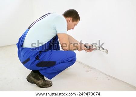 Electrician installing wall sockets - stock photo