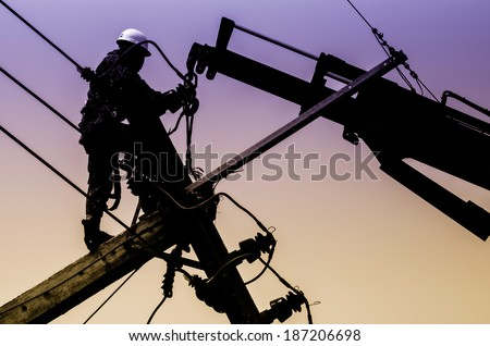Electrician lineman repairman worker at climbing work on electric post power pole - stock photo