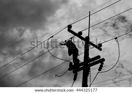 Electrician lineman repairman worker at climbing work on electric post power pole.At the time of the dark clouds cream