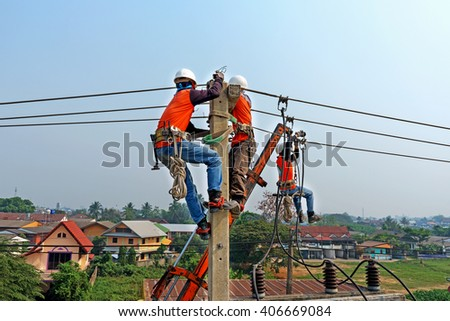 Electrician lineman repairman worker at climbing work on electric post power pole, Thai language same safty fist in English language - stock photo