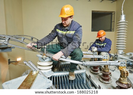 Electrician lineman repairman worker at huge power industrial transformer installation work - stock photo