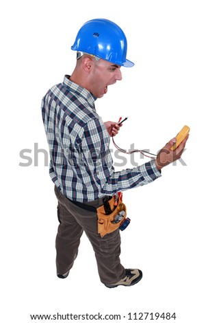 electrician looking at his measurement tool and screaming of surprise - stock photo