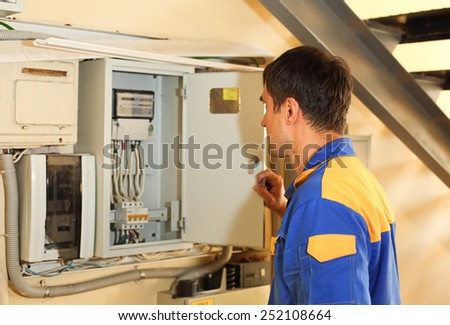 Electrician looks  into electric line distribution fuseboard - stock photo