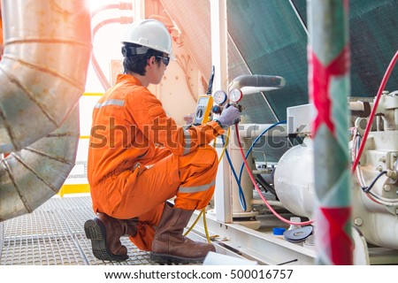 Electrician operator inspect and checking heating ventilated and air conditioning (HVAC), air conditioning, electrical service in offshore oil rig platform while worker charging refrigerant in system.