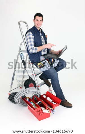 Electrician perched on step ladder - stock photo