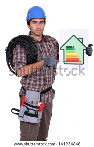 Electrician pointing to energy rating poster - stock photo