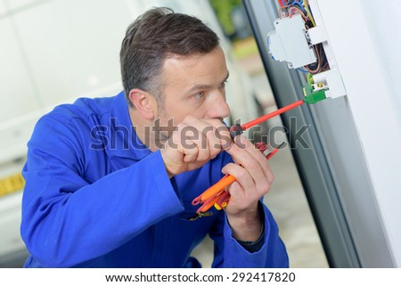 Electrician prodding around at a fusebox - stock photo