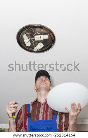 Electrician sets the lamp on the ceiling. - stock photo