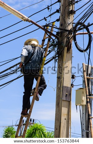 Electrician stays on the tower pole and repairs a wire - stock photo