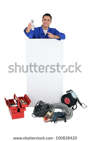 Electrician stood by poster pointing at mobile telephone - stock photo