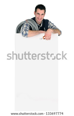 Electrician stood by publicity panel - stock photo