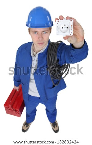 Electrician stood with socket and tool box - stock photo