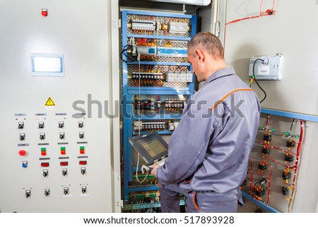 stock photo electrician testing industrial machine electrician builder engineer screwing equipment in fuse box 517893928 electrician testing industrial machine electrician builder stock industrial fuse box at cos-gaming.co