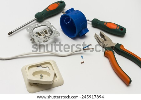 Electrician tools, cable, box for installation of sockets and disassembled outlet before installing close-up.