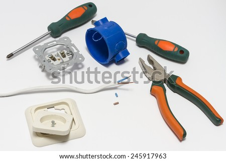 Electrician tools, cable, box for installation of sockets and socket disassembled before installation.