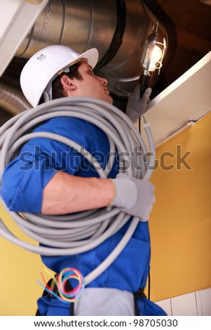 Electrician wiring an industrial loft space - stock photo