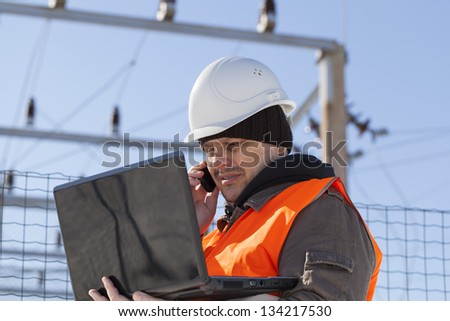 Electrician with PC and cell phone near the electricity substation - stock photo