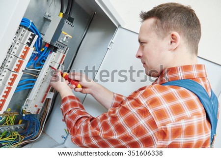 electrician with screwdriver fixing high voltage switching electric actuator in fuse box - stock photo