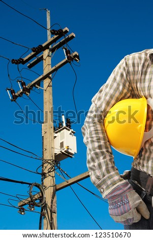Electrician worker at work against electric post and blue sky background - stock photo