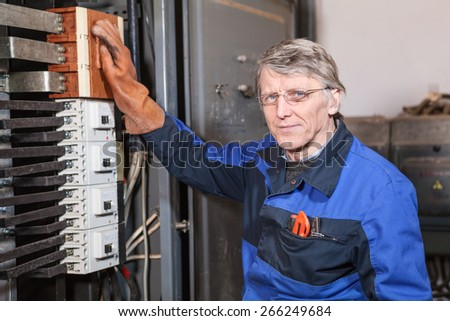 Electrician worker in rubber glove take on switches - stock photo