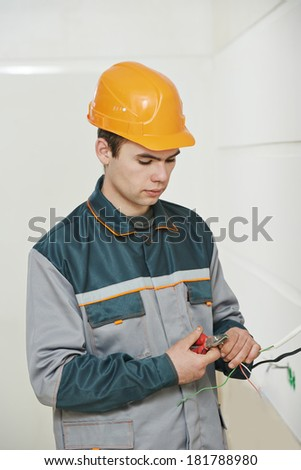 electrician worker in uniform working with cable wiring - stock photo