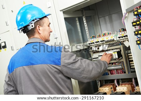 electrician worker with switching on the electric power switch in fuse board - stock photo