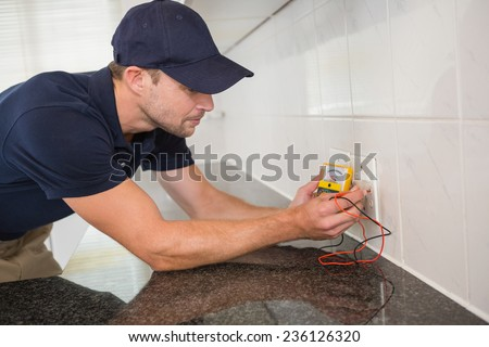 Electrician working at plug socket in a kitchen - stock photo