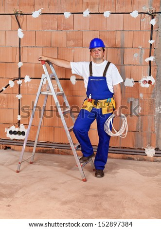 Electrician working in a new building - installing wires and making connections - stock photo