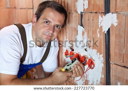 Electrician working in a new building - installing wires in wall fixtures - stock photo