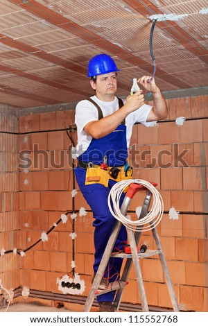 Electrician working on ceiling wires standing on ladder - stock photo